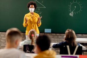 Teacher standing by chalkboard wearing a mask at the head of the classroom