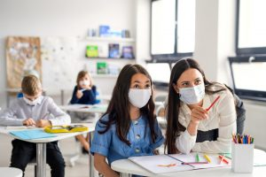 Teacher wearing a mask showing a concept to a young girl