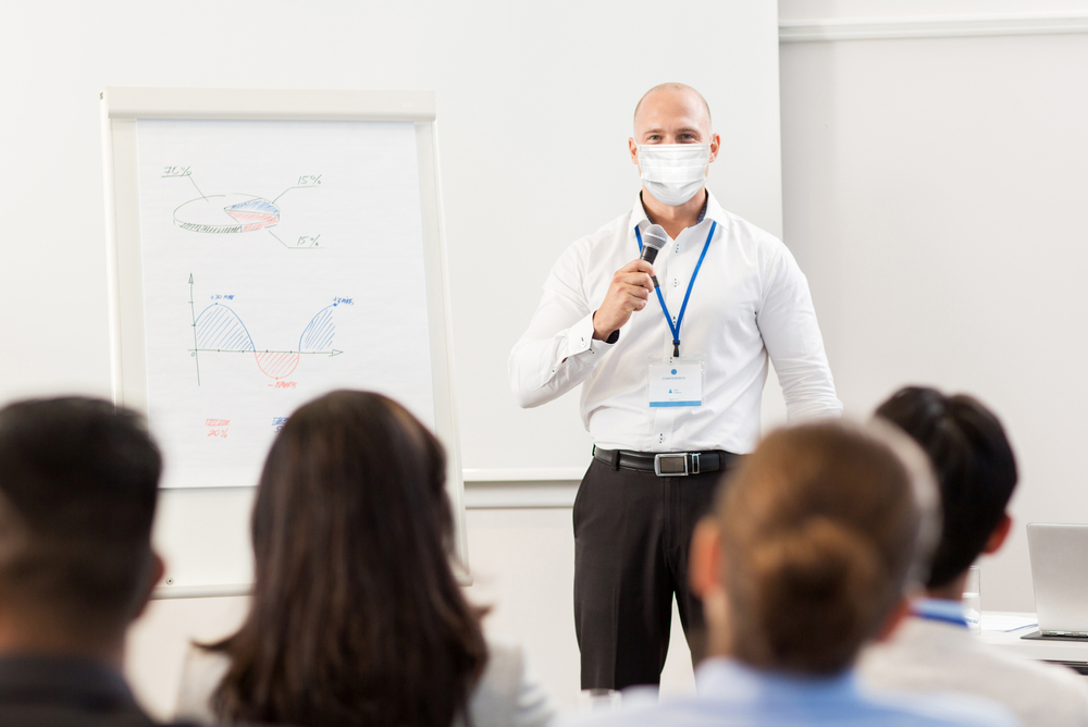 Teacher in the classroom wearing a mask using a microphone