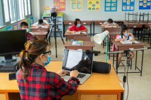 Teacher sitting at desk with laptop teaching class wearing masks