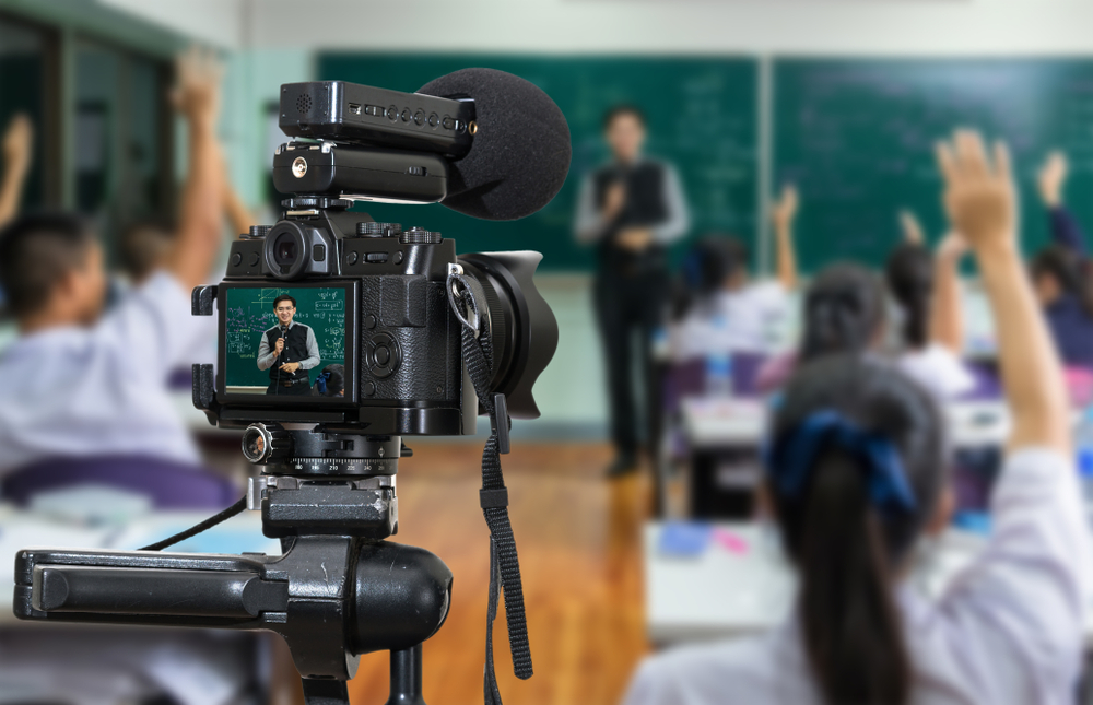 Teacher in a classroom using video and a microphone